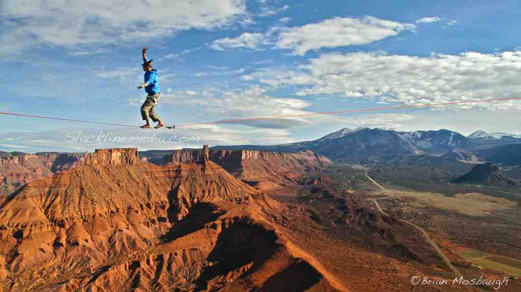 """Local Moab climber/highline developer, Ryan Matson, takes a casual stroll in paradise atop Parriott Mesa on """"Rim with a View."""" This location offers access to some of the most amazing tower climbs in the area with equally amazing views of Utah's staggering landscape."""